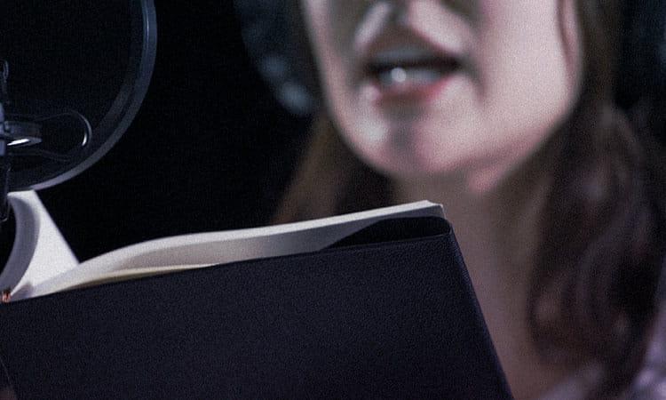 写真:台本を読むナレーター